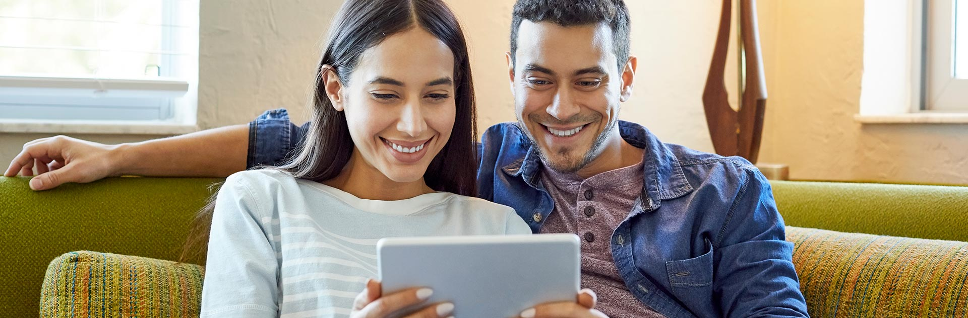 couple on sofa with tablet